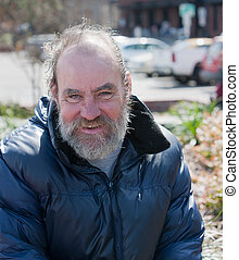 Portrait of happy homeless man outdoors during the day.