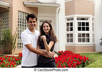 Happy homeowners infront of new house - Real estate: Couple...