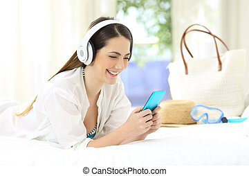 Happy hotel guest listening to music on vacations