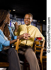 Happy hour - Young African couple sitting at a bar
