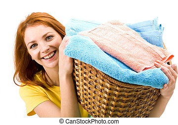 Portrait of young female holding basket full of colorful towels and smiling to camera