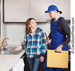 housewife watching as worker repairing  water lines
