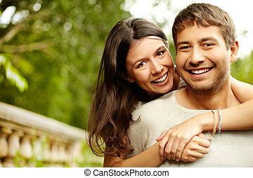 Happy hug - Girl hugging his boyfriend, both looking at the...