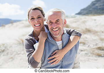 Happy hugging couple on the beach looking at camera on a...