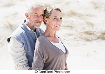 Happy hugging couple on the beach looking away