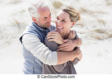 Happy hugging couple on the beach looking at each other on a...