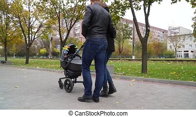 Happy husband and wife kissing in a park near baby buggy