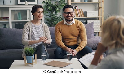Happy husband and wife talking to psychologist during couple...