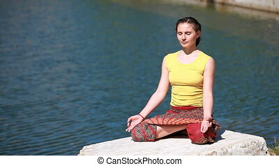 Happy in harmony - Girl sitting on a rock near the water and...