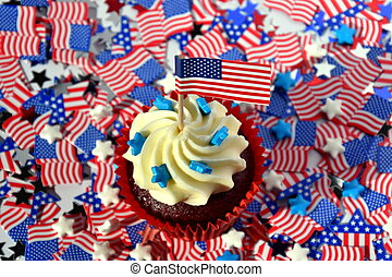 Happy Independence Day, celebration, patriotism and holidays concept - close up of glazed cupcakes or muffins decorated with american flags at 4th july party