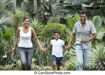 Happy indian family running together outdoors
