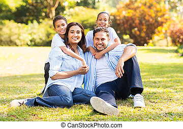 happy indian family sitting on grass