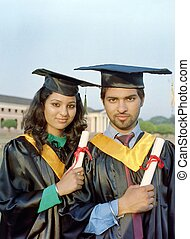 Happy Indian Graduates with Diplomas in hand.