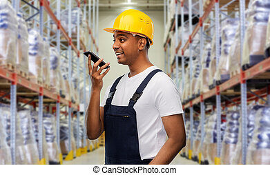 happy indian loader recording voice on smartphone - logistic...