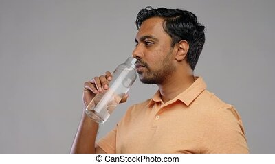 sustainability, consumerism and eco friendly concept - happy smiling indian man drinking water from reusable glass bottle grey background