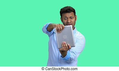 Happy Indian man playing video game on tablet pc. Emotional guy playing game on digital tablet against color background. People, modern technology and leisure concept.