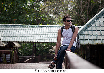 Happy indian man sitting on railing
