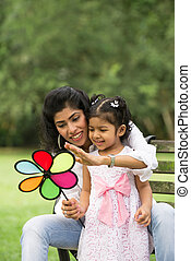 Happy Indian mother and daughter playing in the park. Lifestyle