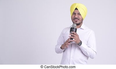Happy Indian Sikh businessman presenting something with...