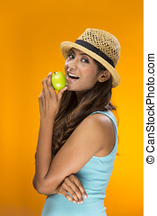 Happy Indian Woman holding an apple on orange background.