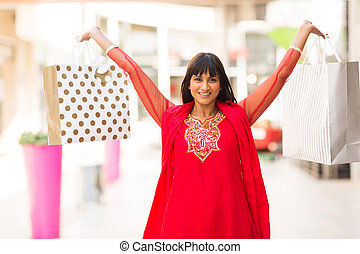 indian woman holding shopping bags in mall