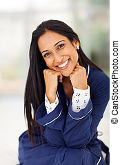 happy indian woman sitting in bedroom