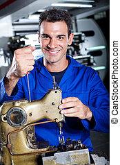 industrial mechanic repairing sewing machine
