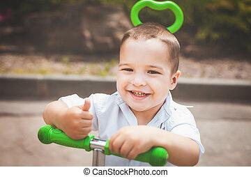happy infant boy on a trike