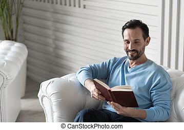 Happy intelligent man reading a book