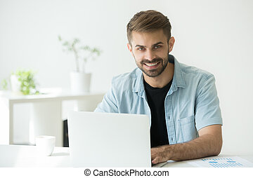Happy intern or marketing manager using computer looking at came