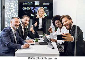Happy international creative diverse business team in formal wear, taking selfie and showing thumbs up, sitting at the table at office. Business, technology, startup and people concept
