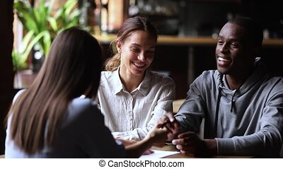 Happy interracial couple customers sign loan investment contract handshake agent