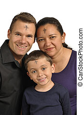Happy interracial family with sign of cross on foreheads celebrating Ash Wednesday