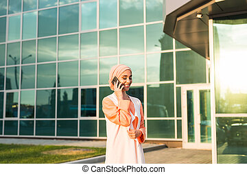 happy islamic woman using smart phone