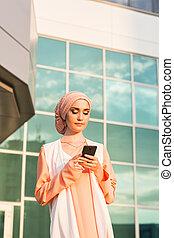 happy islamic woman using smart phone