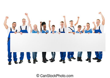 Happy Janitors With Arms Raised Holding Blank Billboard