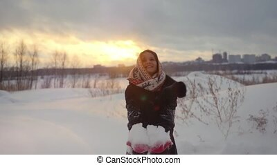 Happy joyful beautiful woman having fun outdoors throwing snow in winter snowy nature in slow motion during sunset.