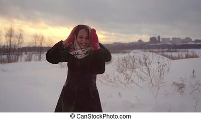Happy joyful beautiful woman having fun outdoors spinning around in winter snowy nature in slow motion during sunset. 1920x1080