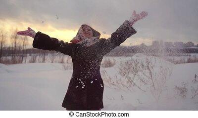 Happy joyful beautiful woman having fun outdoors throwing snow in winter in slow motion during sunset. 1920x1080