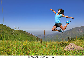 Happy joyful girl jumping against the blue sun and mountains