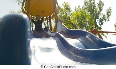 Happy joyful kid sliding down a blue slide on a playground in a park