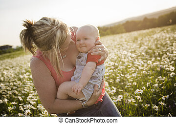 happy joyful mother with son daisy field