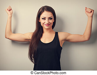 Happy joyful strong young woman showing muscle biceps with smiling. Toned portrait