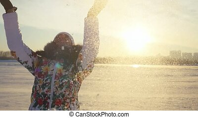 Happy joyful woman having fun and throwing the snow in winter field on sunset city background in slow motion with lense flare effects.