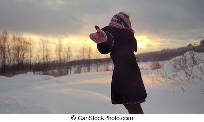 Happy joyful woman having fun outdoors spinning around in winter snowy nature in slow motion during sunset.