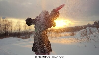 Happy joyful woman having fun outdoors throwing snow in winter snowy nature in slow motion during sunset. 1920x1080