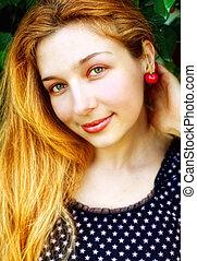 Happy joyful woman with cherry fruit at ear