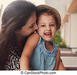 Happy joying kid girl embracing with beautiful mother on summer background. Closeup toned portrait of love family