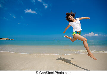 happy jump at the beach - young beautiful girl jumping...