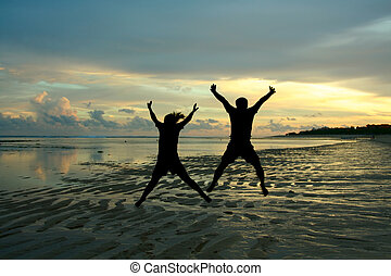 Happy jumping people - Two people in silhouette jumping ...
